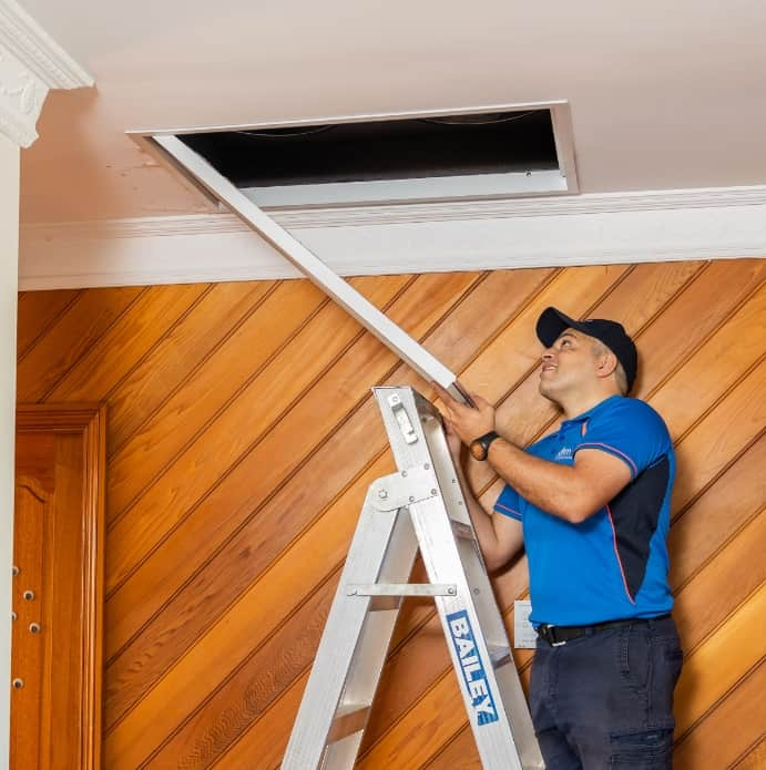A man opening the ceiling aircon